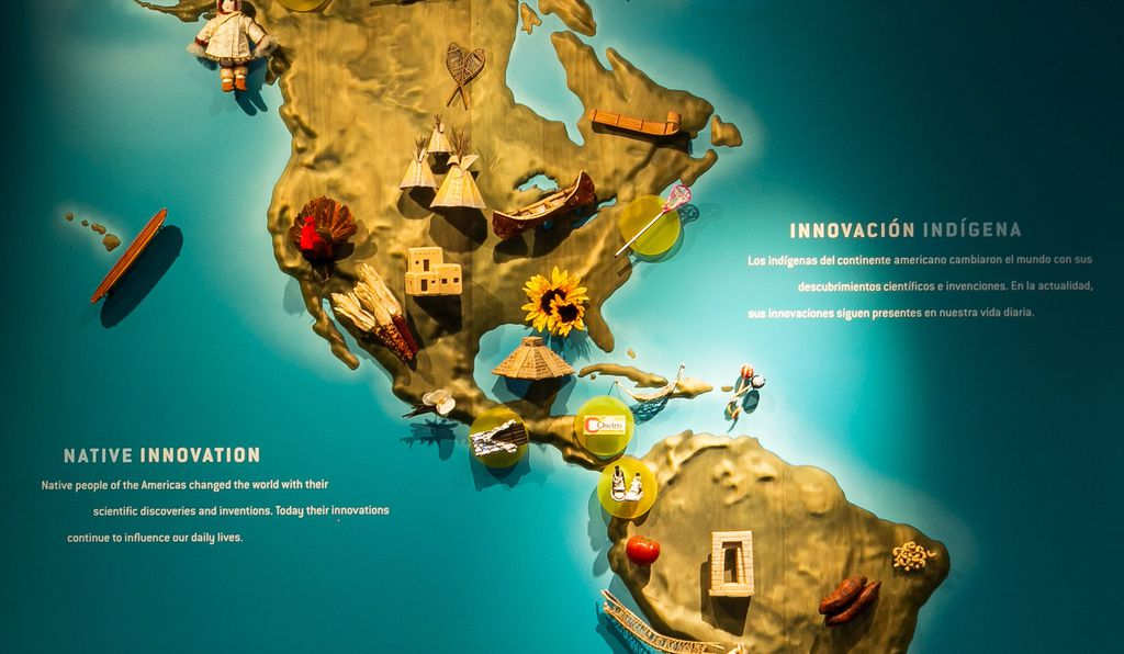 A wall-size map of the Americas is studded with miniature  products first developed by indigenous people. A canoe hovers above the Great Lakes, corn over western Mexico, and a kayak above northern Canada.