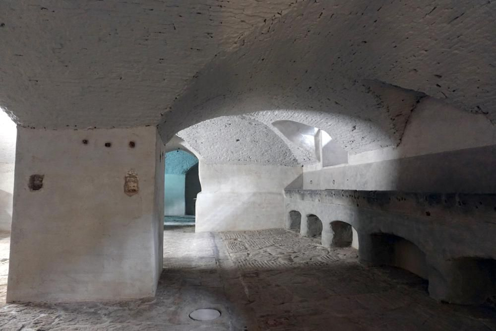 A view of a shadowy white-plastered room, with curved and sloping ceilings and earthen floor
