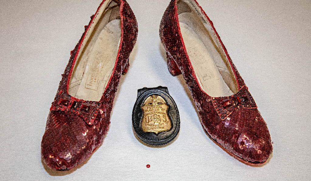 The recovered pair, along with an FBI badge. The single sequin shown here was found at the crime scene at the Judy Garland Museum, from which a pair of Ruby Slippers went missing in 2005.