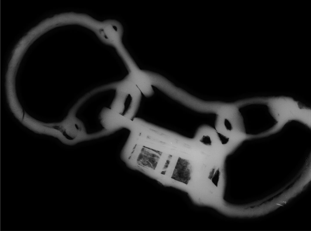 A black and white x ray image depicting the same set of shackles, with the small complicated internal mechanisms of the padlock, center, thrown into relief