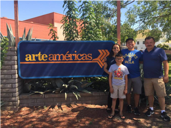 Image of Maya Castillo standing outdoors with three of her male family members next to the Arte Americas sign.