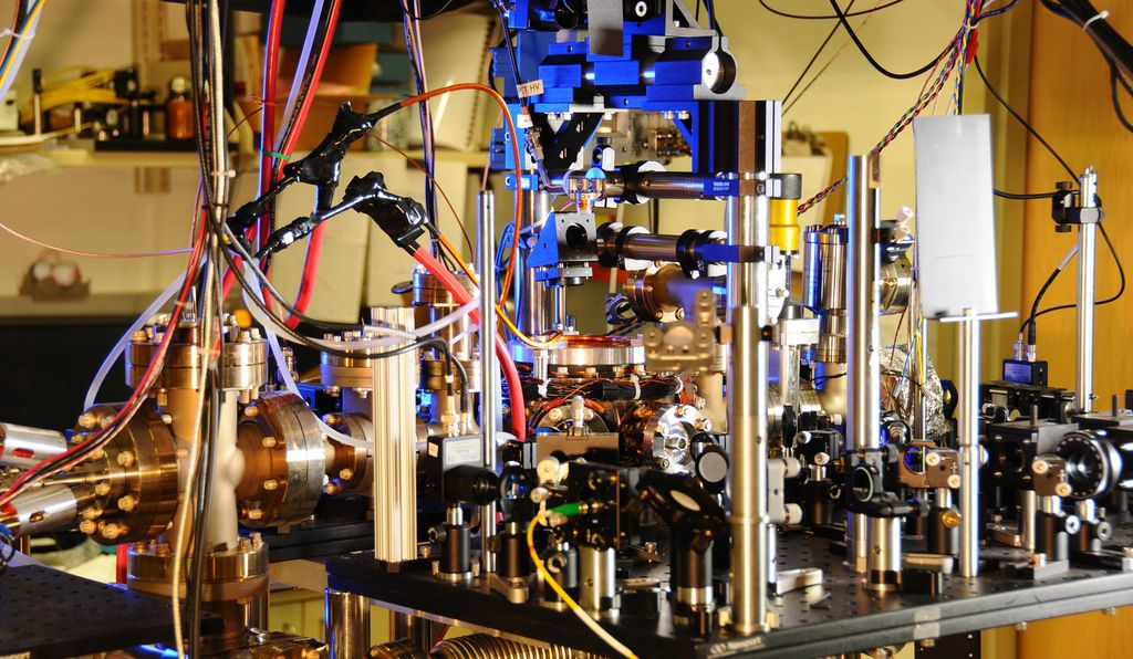 NIST's ultra-stable ytterbium lattice atomic clock. Ytterbium atoms are generated in an oven (large metal cylinder on the left) and sent to a vacuum chamber in the center of the photo to be manipulated and probed by lasers. Laser light is transported to the clock by five fibers (such as the yellow fiber in the lower center of the photo).
