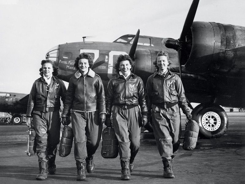 Women Airforce Service Pilots (left to right) Frances Green, Margaret Kirchner, Ann Waldner, and Blanche Osborn pass a line of Boeing B-17s