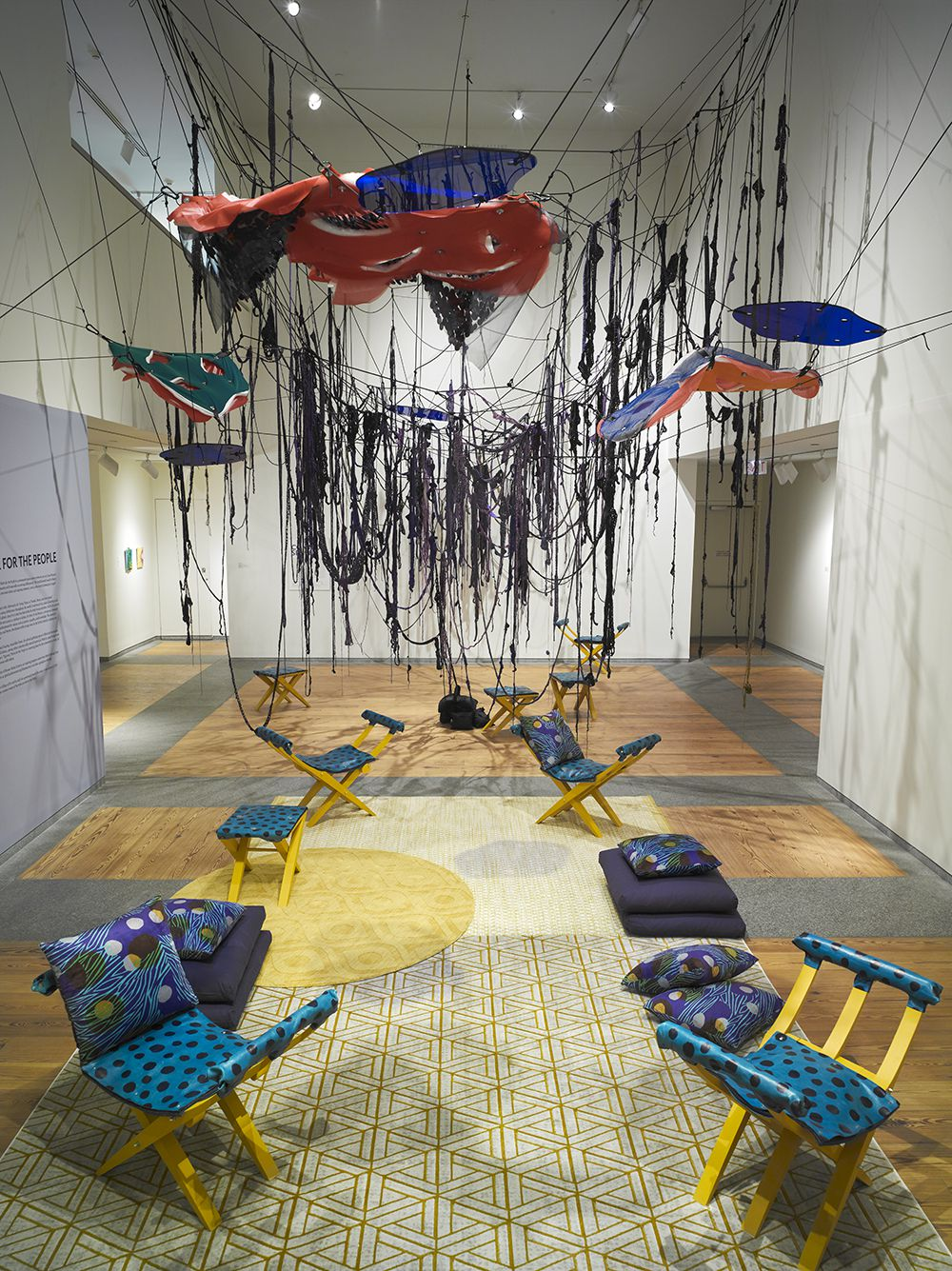 Gallery installation of blue and yellow patterned chairs, yellow patterned carpets, blue patterned pillows, and red, green, and blue hanging from the ceiling.