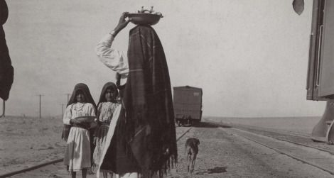 An Isleta woman and her children sell goods alongside a train track, circa late 1880s to early 1900s