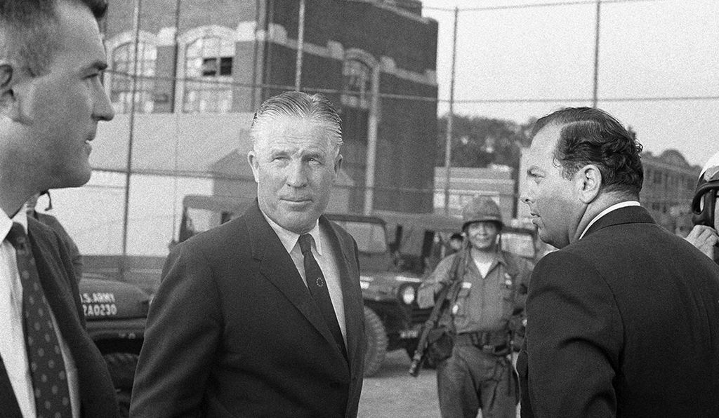 Gov. George Romney, center, confers with Mayor Jerome Cavanagh of Detroit as National Guardsmen standby in a part of Detroit that was ravaged by rioters, July 24, 1967.