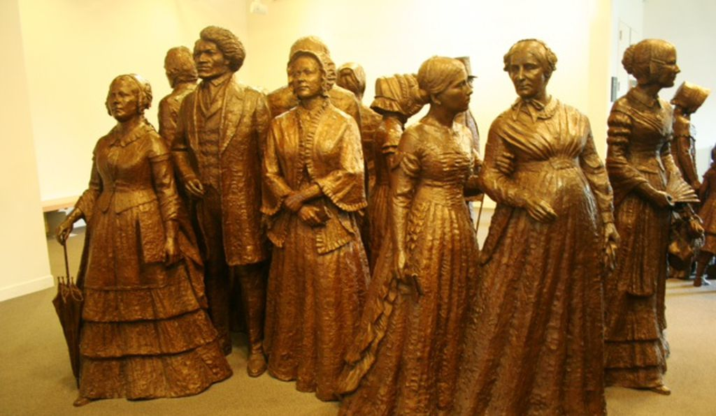 A statue in the interpretive center for the Women's Rights National Historical Park depicts the first wave of suffragettes along with ally Frederick Douglass.