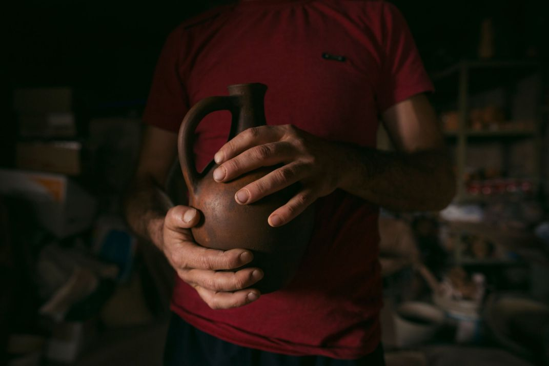 A dark clay jug is clasped in a man's hands.