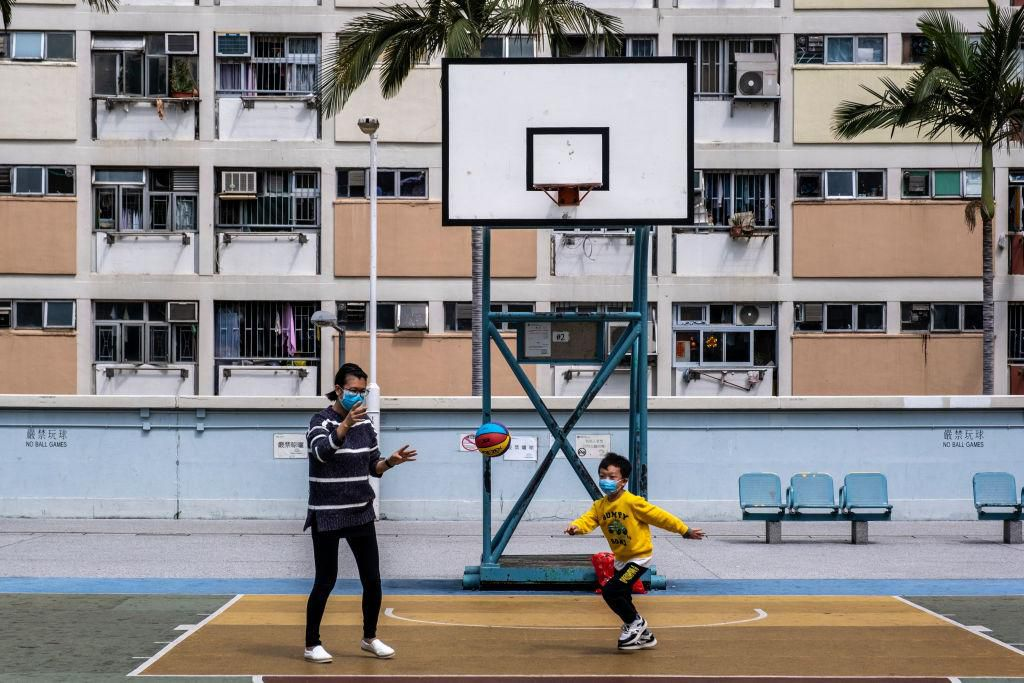 A woman and a boy wear masks as they play basketball in Hong Kong.jpg