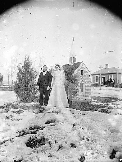 Newlyweds in front of small brick church