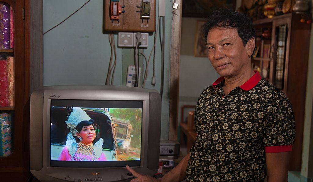 Mor Me Noe, a famous nat kadaw in Mandalay, showing the video of their performance at a spirit festival