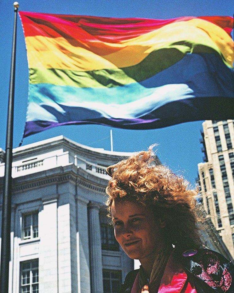 A woman with brown curly hair stands and smiles in front of a rainbow colored flag blowing in the wind in front of a stately white building and blue sky