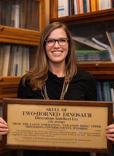 Diana Marsh holds a wood exhibit label from the Smithsonian's early fossil hall with bookshelves behind her.