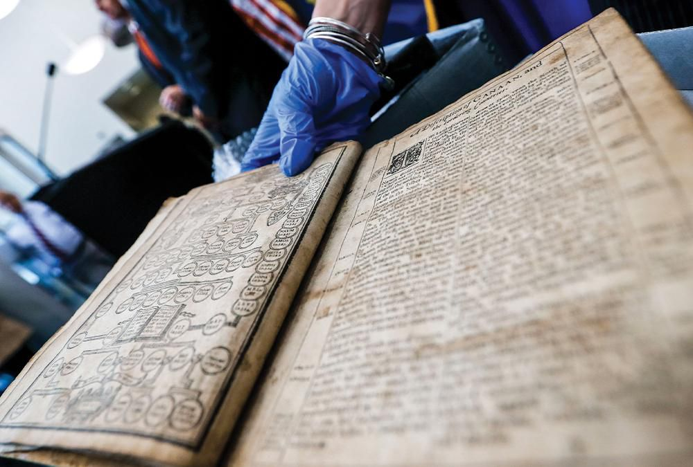 bible being held by blue-gloved hand