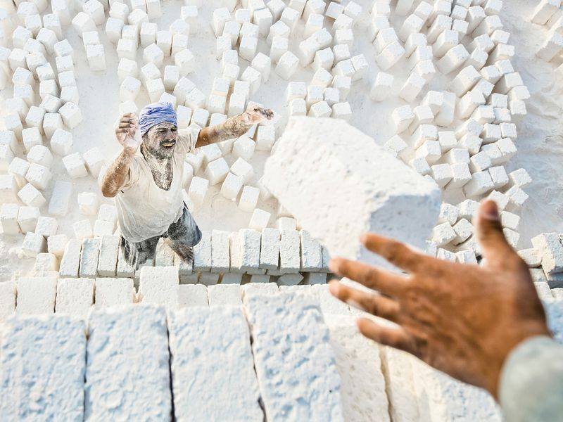 At one of white limestone quarries workshops in Minya city, Egypt.I think he's a genius laborer,I photographed this shot in the last phase of making and producing the white limestone,it' called filling time,the workers are filling the white stones into the vehicles to be ready for trading in the market, actually they have a very nice way in the filling,by throwing it in the vehicles,and each stone must be in it place beside the other,side by side,he is in hurry to fill thousands of stones.