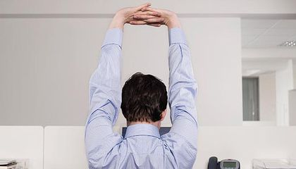 Employee in cubicle stretching