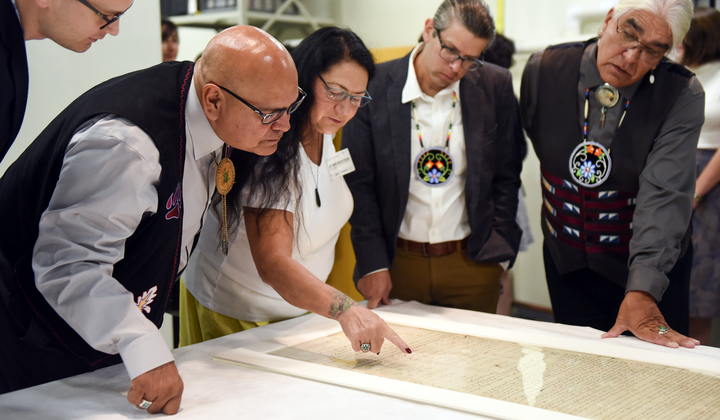Members of a delegation from the Pokagon Band of Potawatomi Indians read names of the signers of the Treaty of Fort Wayne of 1809 as the museum prepares to place the treaty on exhibit. From left: Tribal Council Member Wayne (Alex) Wesaw, Council Chairman John P. Warren, Council Elders Representative Judy Winchester, Tribal Historic Preservation Officer; Jason S. Wesaw, and Council Vice Chairman Robert (Bob) Moody, Jr. National Museum of the American Indian, Washington, D.C., September 2017. (Kevin Wolf/AP Images for National Museum of the American Indian)