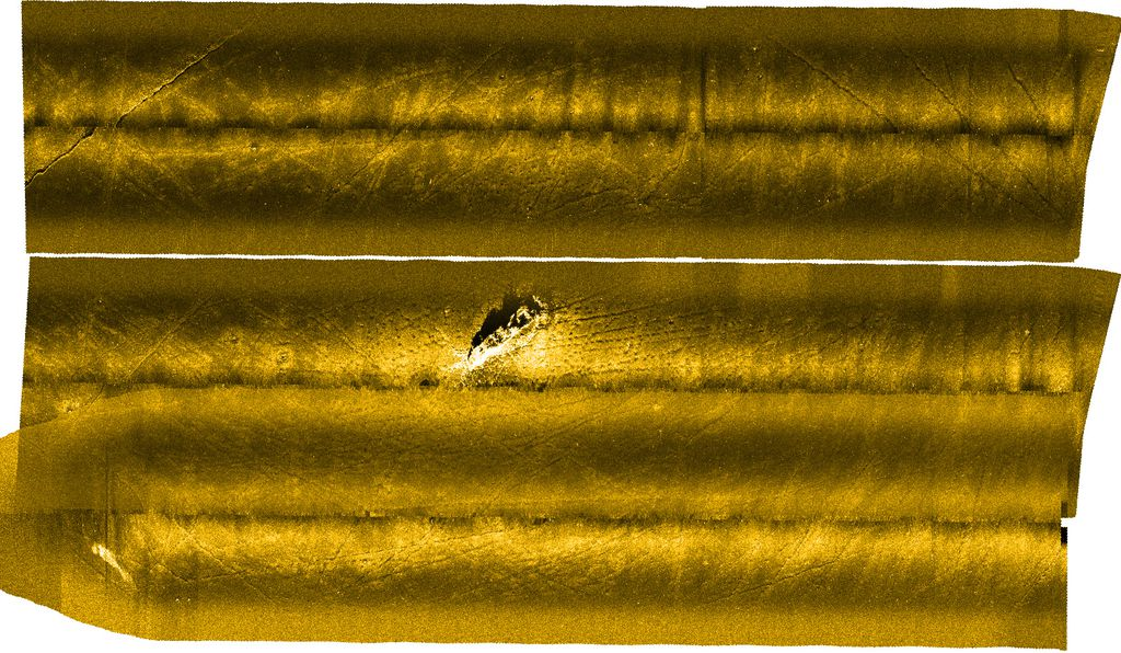 This side-scan sonar image of the Baltic seafloor reveals what could be a scuttled ship full of chemical weapons, and trawl marks from fishing vessels crisscrossing the seafloor nearby.