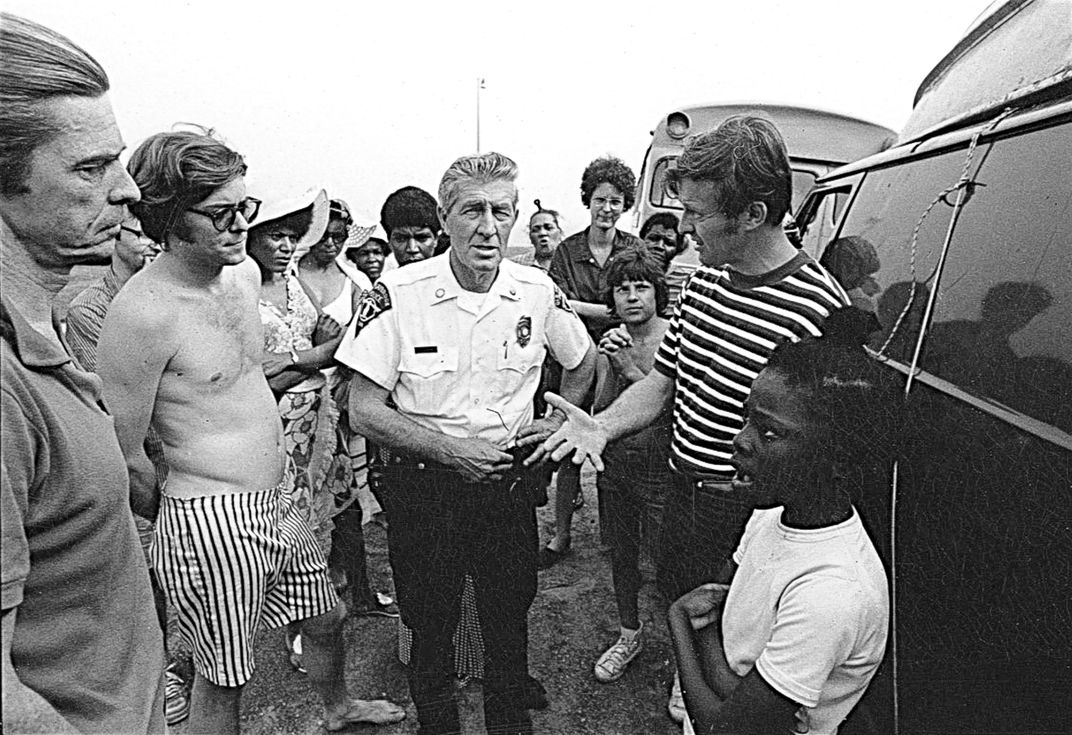 Ned Coll, right, confronted by a local police officer in Madison