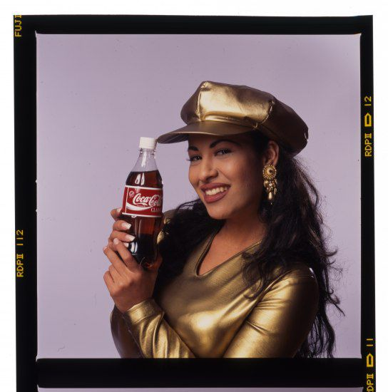 Selena in a gold cap holding a Coca-Cola bottle