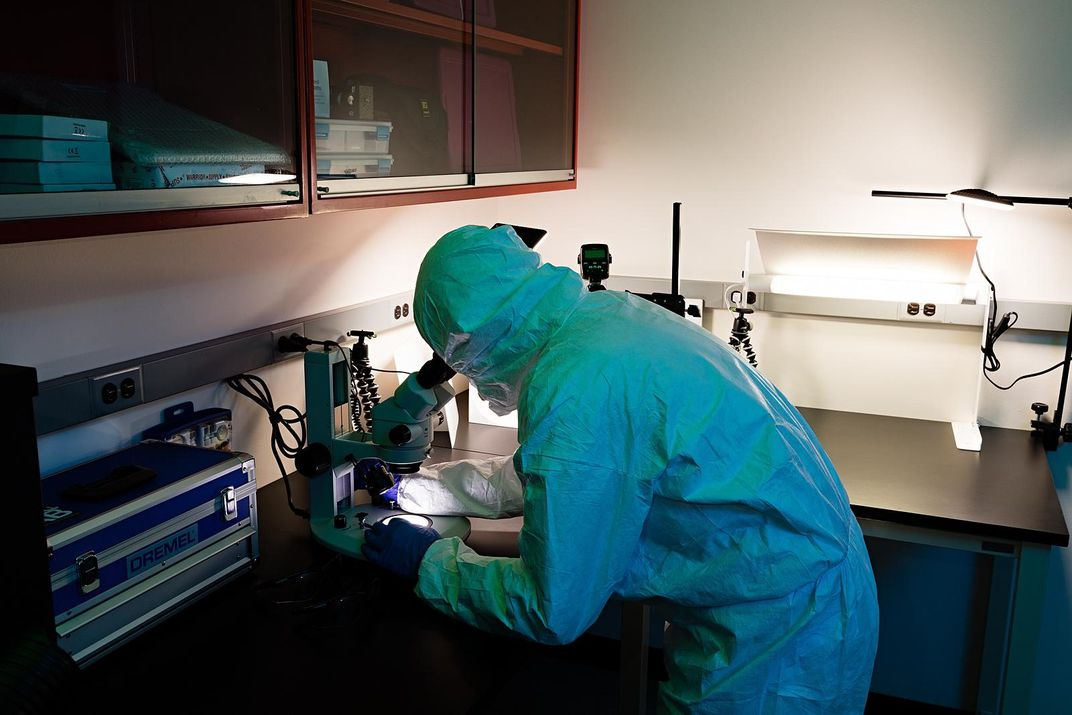 Person in a protective suit looking through a microscope.