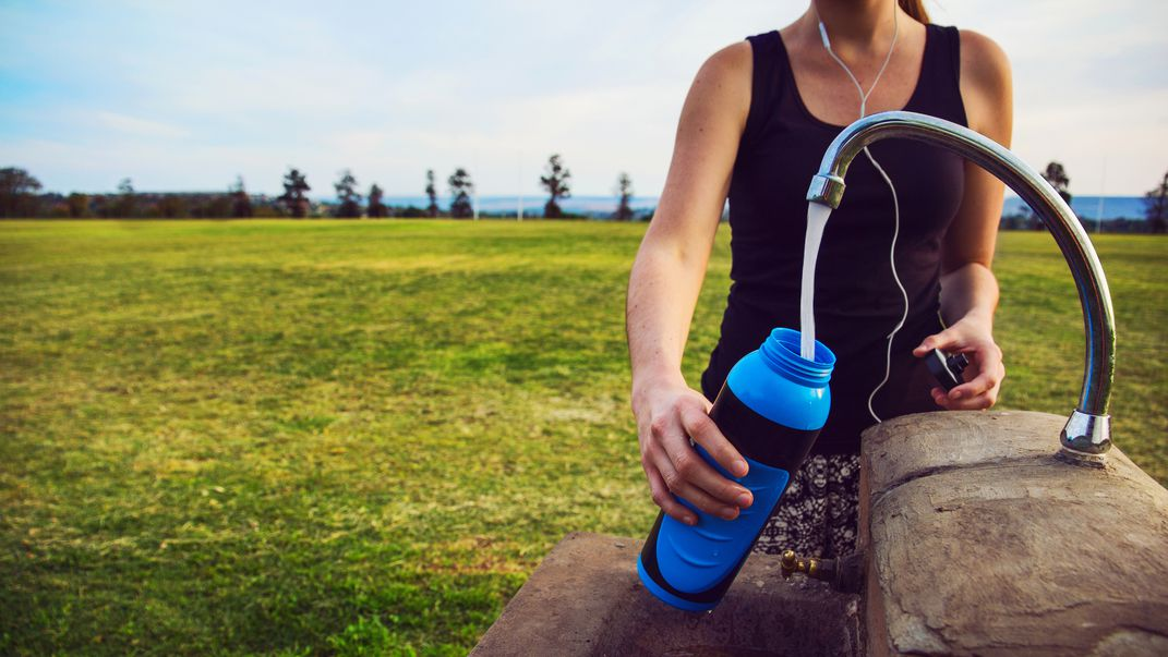 Image of jogger refilling a reusable water bottle.