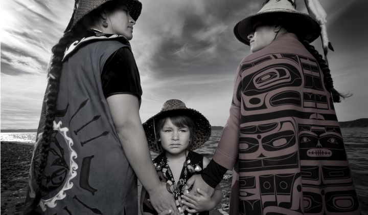 "Darkfeather Ancheta, Eckos Chartraw-Ancheta, and Bibiana Ancheta, Tulalip, Washington. Darkfeather, is pictured with her sister Bibiana and nephew Eckos at the edge of Tulalip Bay. They are wearing traditional regalia prepared for their annual Canoe Journey. Every year, upwards of 100 U.S. tribes, Canadian First Nations and New Zealand canoe families will make ""The Journey"" by pulling their canoes to a host destination Tribe. Canoe families pull for weeks, and upon landing participate in several days and nights of ""protocol"", a celebration sharing traditional knowledge, ancestral songs, and sacred dances. Photo by Matika Wilbur for Project 562. Courtesy of the Artist."