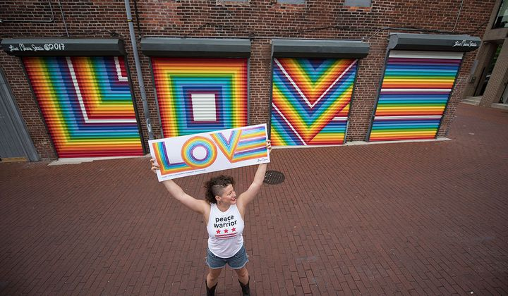 Lisa Marie Thalhammer holds her original LOVE poster with her mural in the background. (Photo by Grant Langford)