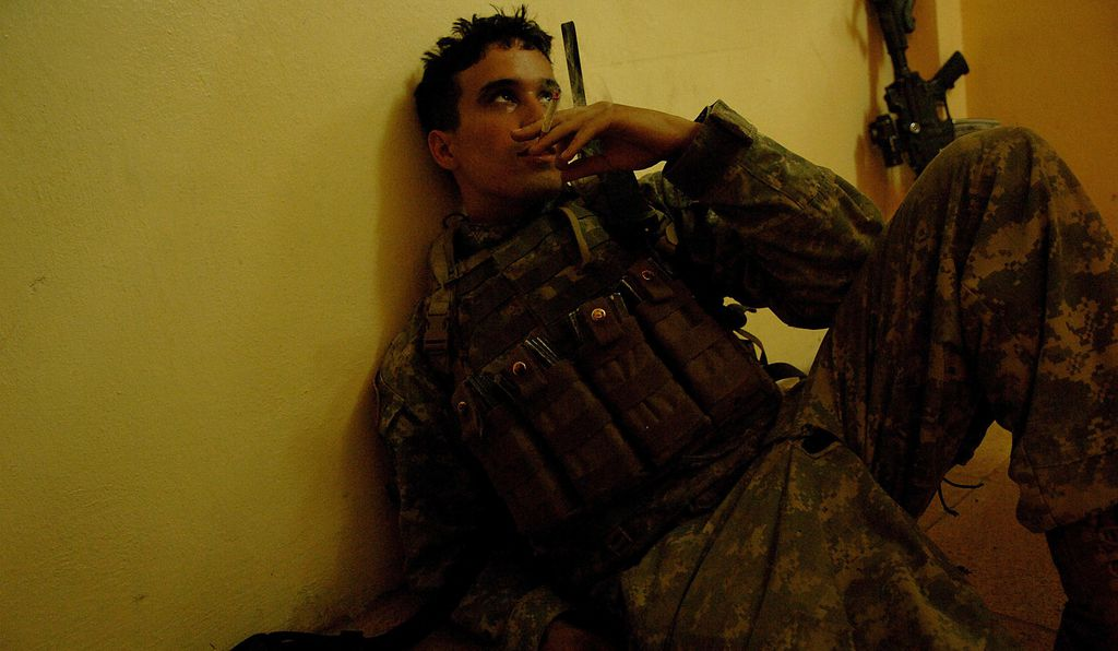 Exhausted from the heat, PFC Valentine Rodriquez from 1st Platoon Charlie Company 1/17th Infantry 172nd Stryker Brigade, Fort Wainwright, Arkansas, sits on the floor resting and smoking a cigarette at an Iraqi Police station, June 21, 2006, during a patrol in Rissalo, Mosul in Iraq.