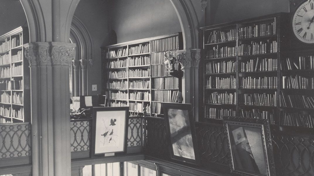 Black and white photograph of library with book shelves and frame pictures.