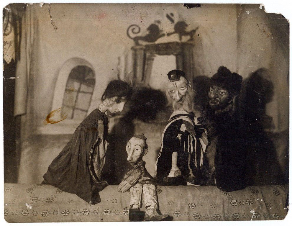 Four puppets stand gathered in the center of a stage displaying with a set of a small village.