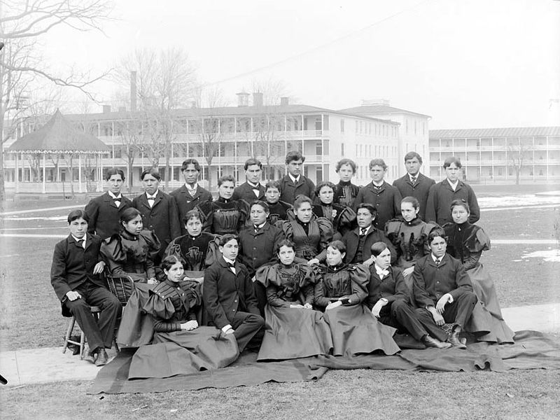 Group_of_Male_and_Female_Students;_Brick_Dormitories_And_Bandstand_in_Background_1879.jpg