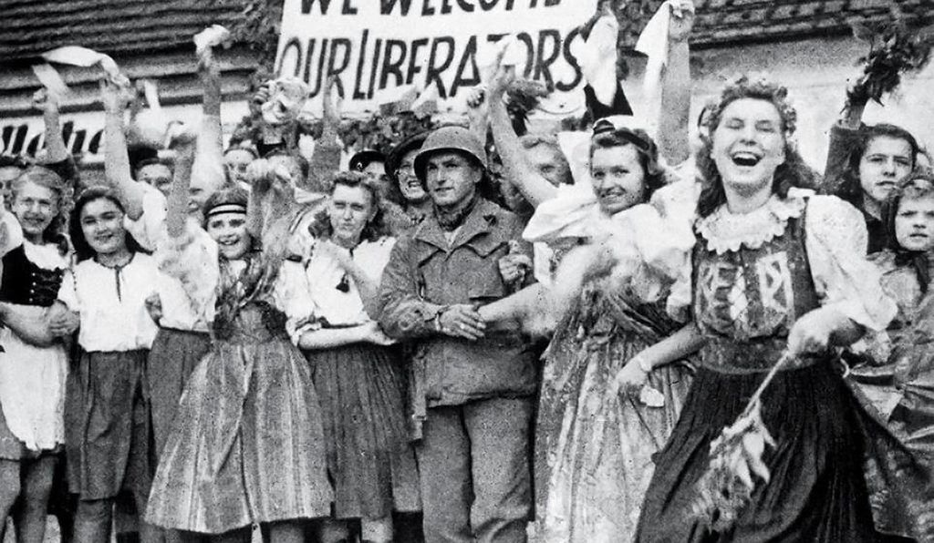 In May 1945, locals in traditional Czech costumes welcome U.S. soldiers to Pilsen, the city that was home to the Skoda Works factory.
