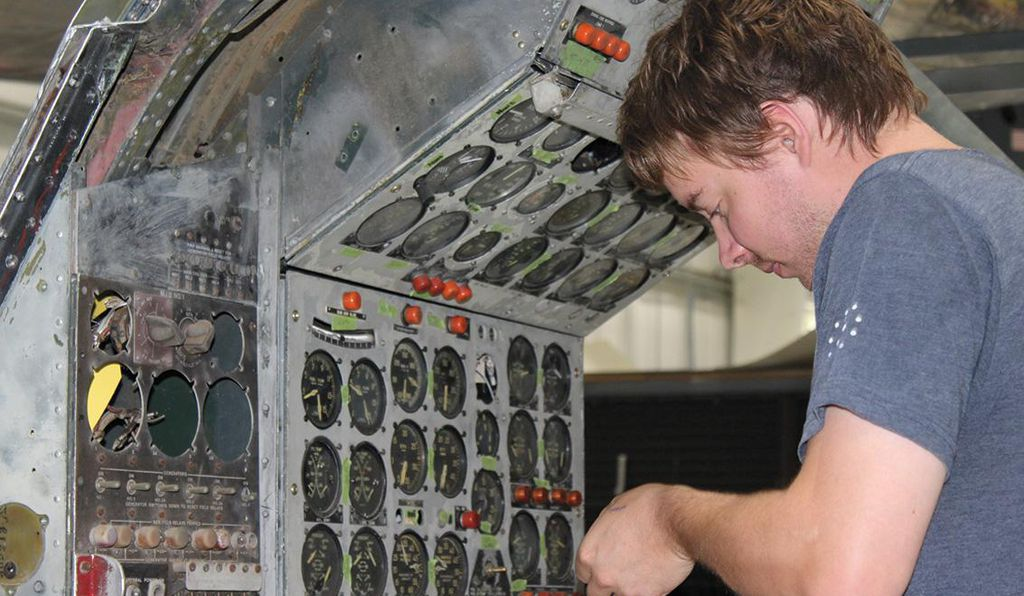Aaron Asche, who is helping to rewire the aircraft, examines the flight engineer's instrument panel.