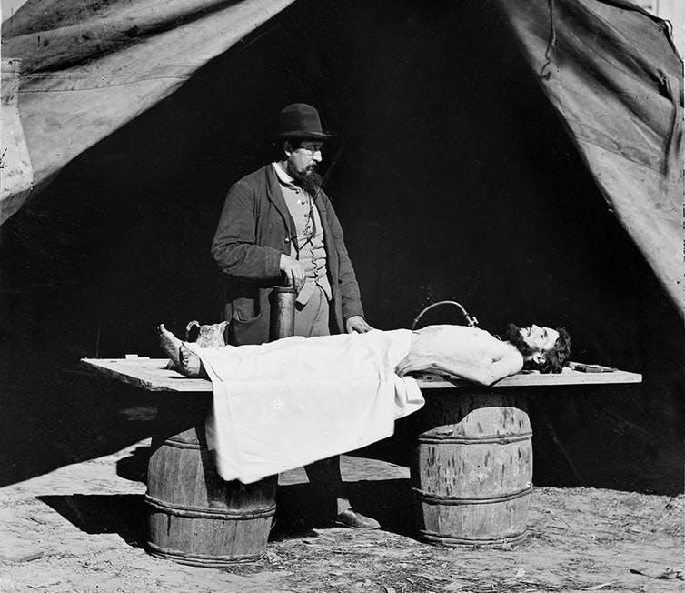 A surgeon embalms a soldier's body during the Civil War
