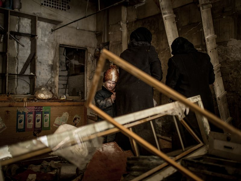 Syria, January 2017 - Destroyed street alley in east Aleppo. Residents who have returned to the streets. A child and his mom search a beauty shop for nail polish an other non broken things.