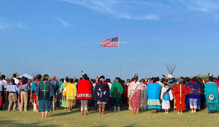 "Members of the Kiowa Gourd Clan Ceremony stand as the flag of Spencer ""Corky"" Sahmaunt is raised. Carnegie, Oklahoma; July 4, 2019. Mr. Sahmaunt served in the U.S. Army during the Korean War and was a member of the Kiowa Black Leggings Warrior Society, as well as the Kiowa Gourd Clan.The Kiowa Flag Song, analogous to the Star Spangled Banner, accompanied the flag-raising. (Photo courtesy of Mari Frances Sahmaunt, used with permission)"