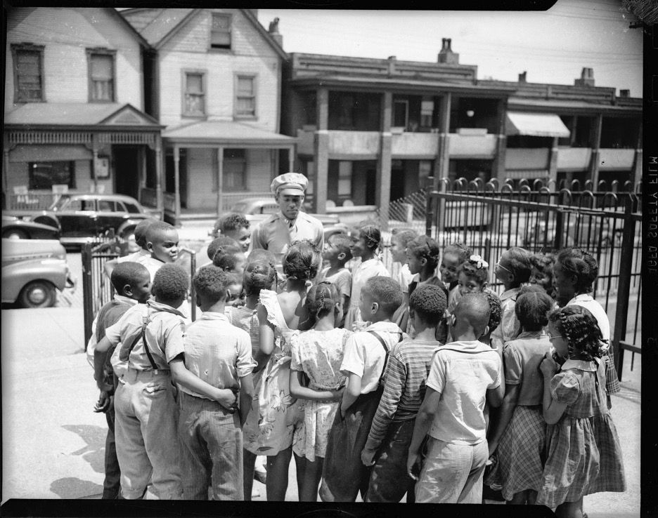 Children gathered around Tuskegee Airman James T. Wiley