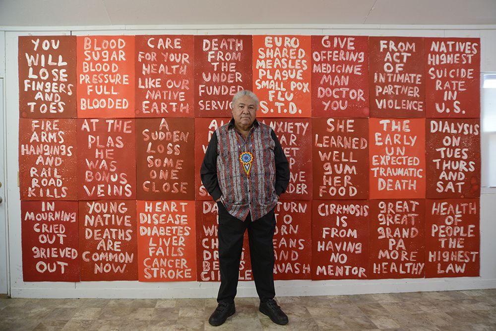 Man standing against a wall full of red canvases with white text