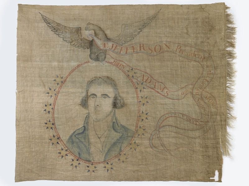 A faded linen banner, frayed on the edges, with a portrait of Jefferson surrounded by a floral garland and an eagle overhead