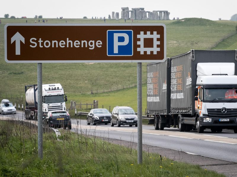 A busy road is in the foreground, with trucks and cars, and a large sign pointing to Stonehenge; the iconic stone structures are visible in the background