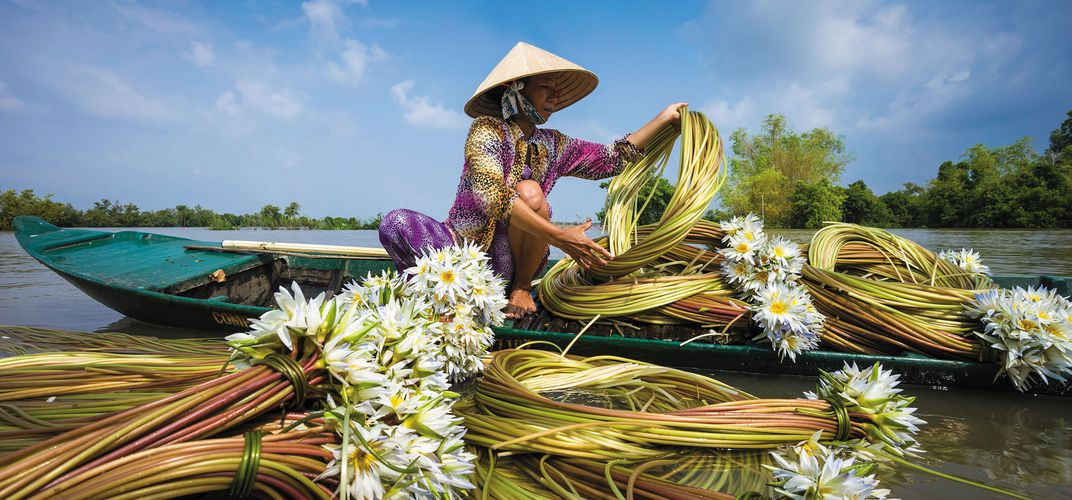 Woman working with flowers on the Mekong. Credit: Nhiem Hoang