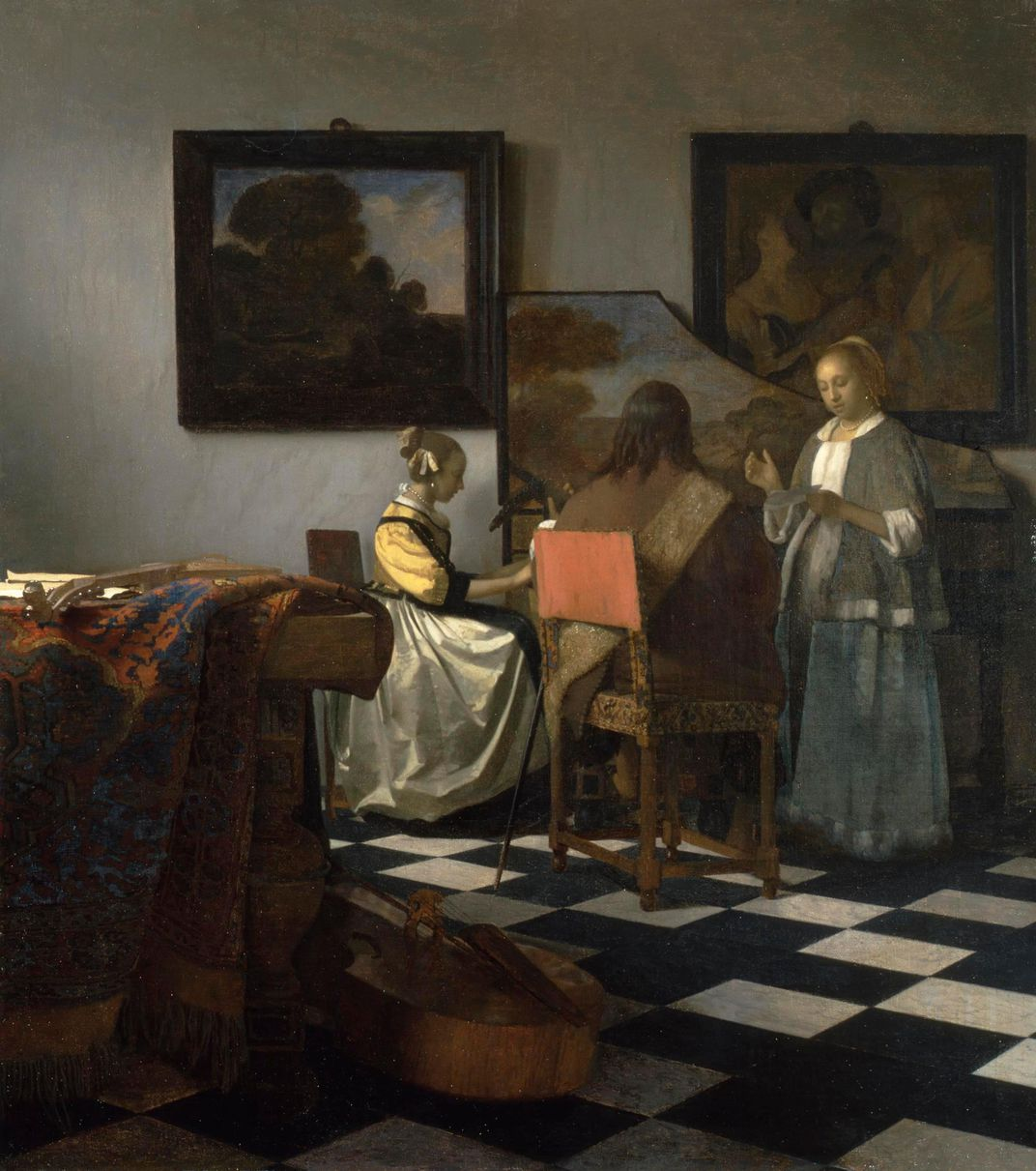 An interior domestic scene of two women and a man performing music