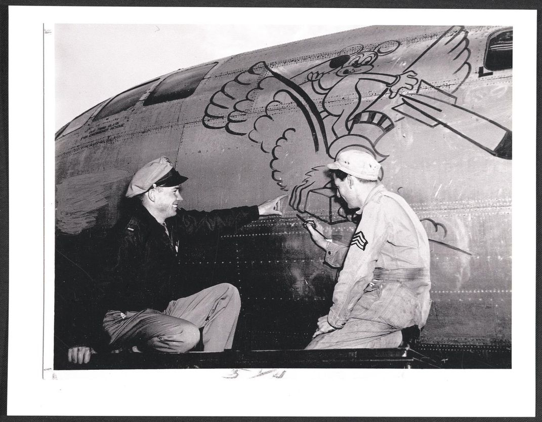 one airman painting a plane while other points