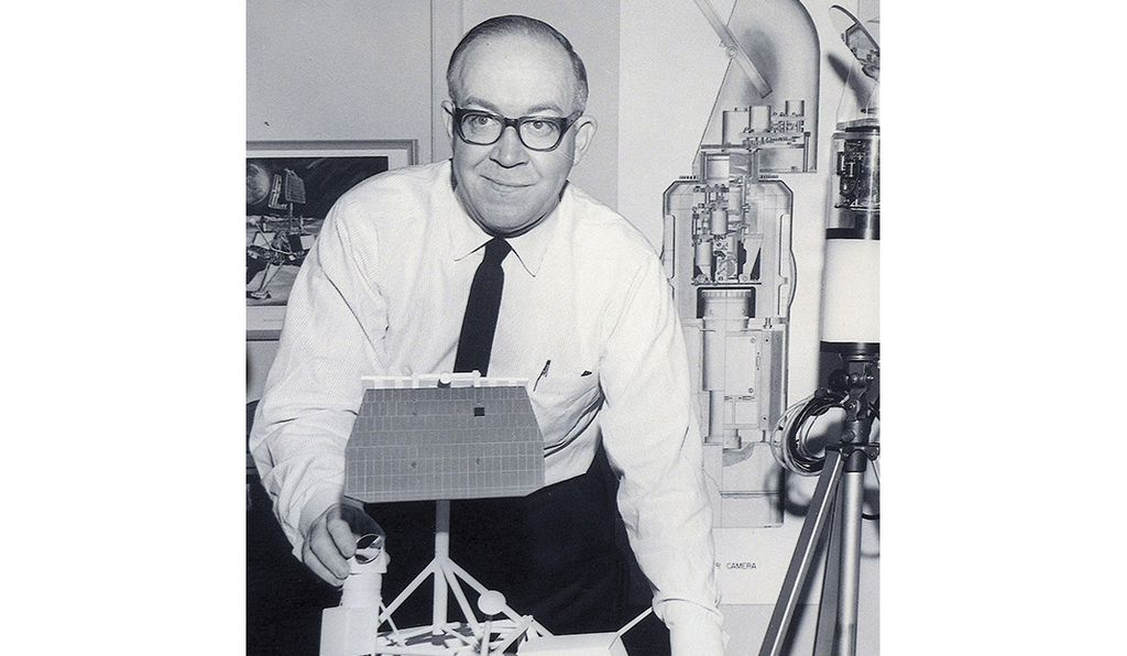 Frank Mellberg in his office in 1966, with a model of Surveyor I in front and a cutaway of the lens in the background.