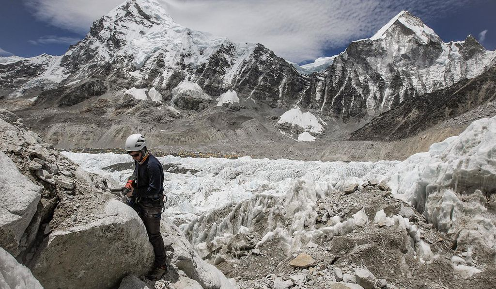 A member of the National Geographic and Rolex Perpetual Planet Everest Expedition team takes a sample from a rock outcrop next to the Khumbu Icefall above Everest Base Camp. For more info on the expedition, go to <a href='https://www.nationalgeographic.com/environment/perpetual-planet/' target='_blank'>www.NatGeo.com/Everest</a>.