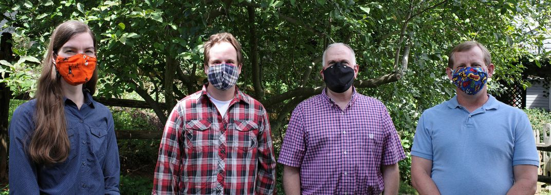 Four people, all wearing masks, stand in front of green leafy trees and smile a few feet apart from one another