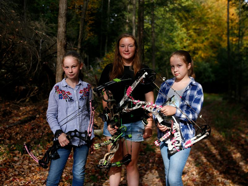 Three girls stand with their bows outside of Travis Archery in Woodbourne, New York.