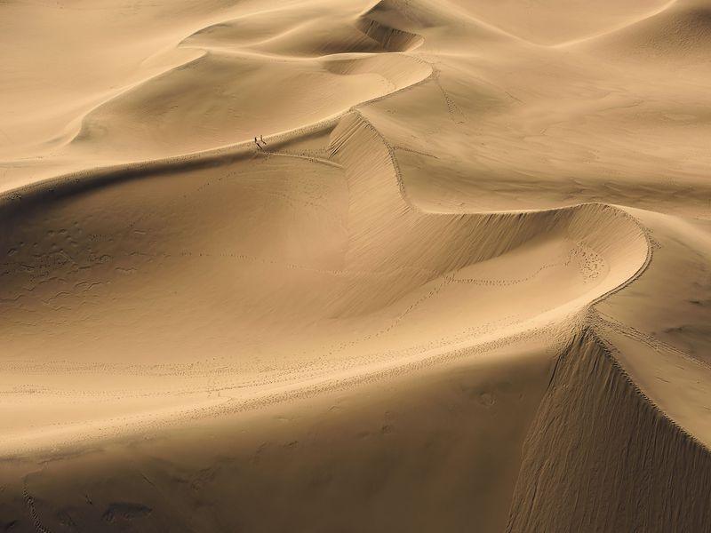 Death Valley's dunes are beautiful and spectacular to explore. Here, you see two brave souls walking on the edge of these massive mountains of sand. Death Valley National Park, California. Aerial Image.