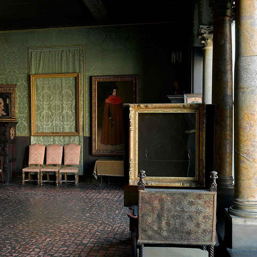 A luxuriously decorated room with green silk on the walls and two empty gilded frames visible